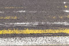 Pedestrian crossing. Erased bands of white and yellow on the pedestrian crossing the road. photo close-up, side view Royalty Free Stock Photo