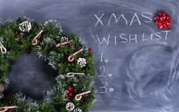 Erased black chalkboard with holiday wreath plus text writing. Wreath, gift bow and candy canes on erased chalkboard with Christmas wish list written on board Stock Photo
