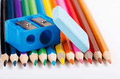 Eraser, colored pencils and sharpener on white background Stock Photos