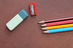 Eraser, writing pencils and a sharpener on a brown leather backg Royalty Free Stock Images