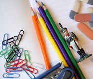 Erasers, colored pencils, toy soldier and stepler. On the notebook Royalty Free Stock Images