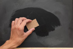 Erasing chalk from the blackboard Stock Photography