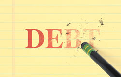 Erasing Debt From Ledger. Close up of a black pencil erasing the word, 'debt' printed in red on yellow ledger paper Royalty Free Stock Photo