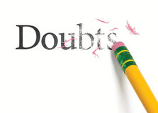 Erasing Doubts. Close up of a yellow pencil erasing the word, 'Doubts.' Isolated on white Stock Image