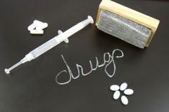 Erasing Drug Addiction. Pills with a syringe, an eraser and the word drugs written on a blackboard Stock Photo