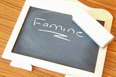 Erasing Famine. This photo shows a blackboard with the word Famine and an eraser Stock Photography