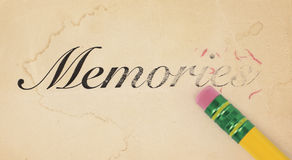Erasing Memories. Close up of a yellow pencil erasing the word, 'memories' from old, yellowed paper Stock Photography