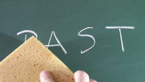 Erasing the past. The word past written with chalk on the blackboard is erased by a man's hand with a wet sponge , conceptual footage about forgetting the past stock footage
