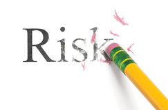 Erasing Risk. Close up of a yellow pencil erasing the word, 'Risk.' Isolated on white Stock Photography