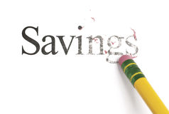Erasing Savings. Close up of a yellow pencil erasing the word, 'Savings'. Isolated on white Stock Photo