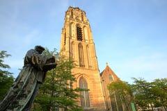 Erasmus Statue, uma escultura de bronze revelada em 1622 e situada no quadrado de Grotekerkplein, com St Lawrence Church Laurensk fotografia de stock