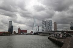 Erasmusbrug a bridge in the middle of Rotterdam with Skyline and dark clouds in the netherlands.  Royalty Free Stock Photos