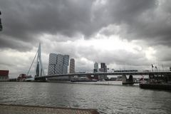 Erasmusbrug a bridge in the middle of Rotterdam with Skyline and dark clouds in the netherlands.  Royalty Free Stock Photography