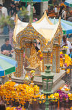 Erawan Shrine at Ratcha-prasong Bangkok,Thailand. Surrounded by flowers and people of faith Royalty Free Stock Photo