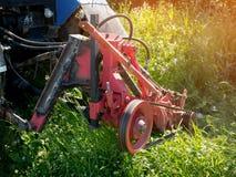 Erba alta di falciatura verde del trattore agricolo in un giorno di estate soleggiato Primo piano Fotografie Stock