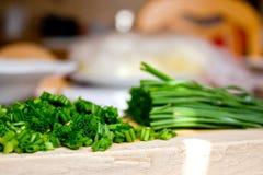 Erba cipollina tagliata sul tagliere nella cucina Fotografia Stock Libera da Diritti