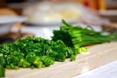 Erba cipollina tagliata sul tagliere nella cucina Immagini Stock Libere da Diritti