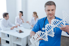 Erba medica intelligente osservando il modello di codice genetico all'ospedale Immagini Stock Libere da Diritti