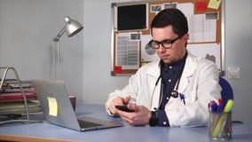 Erba medica maschio in camice con lo stetoscopio che si siede allo scrittorio e che per mezzo dell'orologio astuto video d archivio