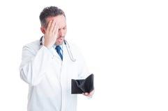 Erba medica turbata o medico che controlla portafoglio vuoto Immagine Stock Libera da Diritti