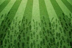 Erba soleggiata di calcio con le stampe della scarpa Immagini Stock Libere da Diritti