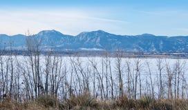 Erbacce, lago congelato e montagne alte distanti Fotografia Stock Libera da Diritti