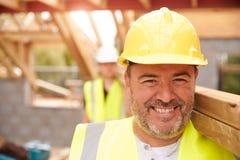 Erbauer-And Apprentice Carrying-Holz auf Baustelle Lizenzfreie Stockbilder