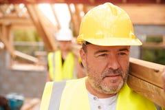 Erbauer-And Apprentice Carrying-Holz auf Baustelle Lizenzfreies Stockbild