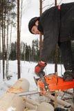 Erbauer behandelt Klotz unter Verwendung der Kettensäge, herausschnitt ringsum Sattelkerbe Lizenzfreies Stockbild