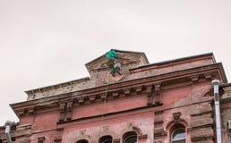 Erbauer-Bergsteiger, der auf die Oberseite der Fassade ein Gebäude hängt Stockfoto