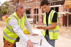 Erbauer On Building Site, das Arbeit mit Lehrling bespricht lizenzfreie stockfotos