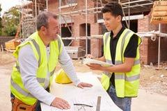 Erbauer On Building Site, das Arbeit mit Lehrling bespricht stockfotos