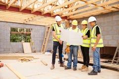 Erbauer On Building Site, das Pläne mit Lehrlingen betrachtet stockfotografie