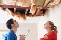 Erbauer-And Client Inspecting-Dach-Schaden stockfoto