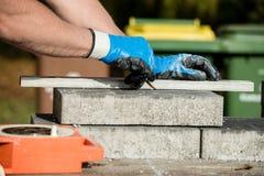 Erbauer, der einen Pflasterstein oder einen Block markiert, um zu schneiden lizenzfreie stockfotografie