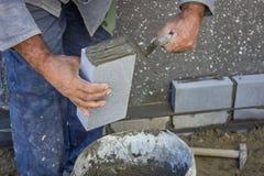 Erbauer, der einen Ziegelstein und mit der Maurerarbeitkelle verbreitend und SH hält Stockbild