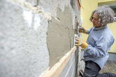 Erbauer, der Fliesen auf eine Wand zutrifft Stockfotografie