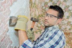 Erbauer, der Fliesen weg von der Wand abbricht Stockbild
