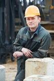 Erbauer in der schmutzigen Arbeitskleidung an der Baustelle Stockbilder
