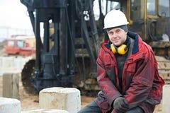 Erbauer in der schmutzigen Arbeitskleidung an der Baustelle Stockbild