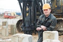 Erbauer in der schmutzigen Arbeitskleidung an der Baustelle Stockfotografie