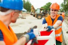 Erbauer, die entlang arbeiten Lizenzfreie Stockbilder