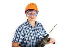 Erbauer in einem Sturzhelm und in Gläsern, die ein Bohrgerät halten Lizenzfreie Stockbilder