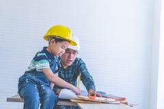 Erbauer Father, der seinen Sohn unterrichtet, das Bauplanpapier zu lesen lizenzfreie stockfotografie