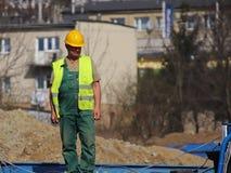 Erbauer im Overall an der Baustelle Reparaturen an der Höhe Aufbau der neuen Gebäude Der Beruf eines Erbauers Hea lizenzfreie stockfotografie