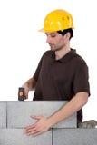 Erbauer mit einer Blockwand Stockbild