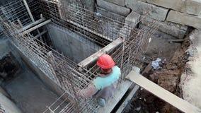 Erbauer mit rotem Schutzhelm am Projektstandort Gebäude der Grundlage stock footage