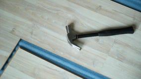 Erbauer nimmt einen Hammer Reparatur der Wohnung, lamellenförmig angeordneten Bodenbelag legend aufbau stock video