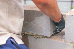 Erbauer setzt einen Schlackenbetonblock für den Bau des Gebäudes talentierte Hände setzt ein brickwall Schlackenbetonblöcke Lizenzfreies Stockfoto