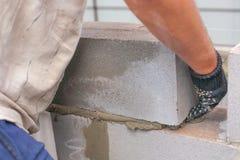 Erbauer setzt einen Schlackenbetonblock für den Bau des Gebäudes talentierte Hände setzt ein brickwall Schlackenbetonblöcke Stockfotografie
